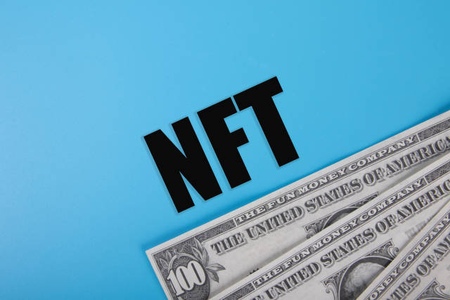 Dollar banknotes and NFT text on blue background