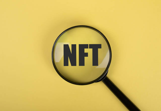 NFT text and magnifying glass on yellow background