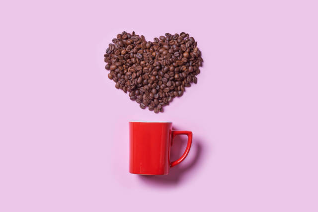 Red coffee cup and raw coffee beans in shape of heart