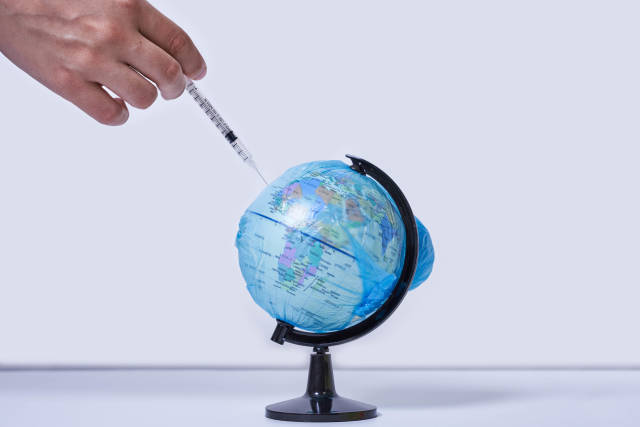 Hand injecting a vaccine into planet Earth. Concept of a cure for all people against the coronavirus