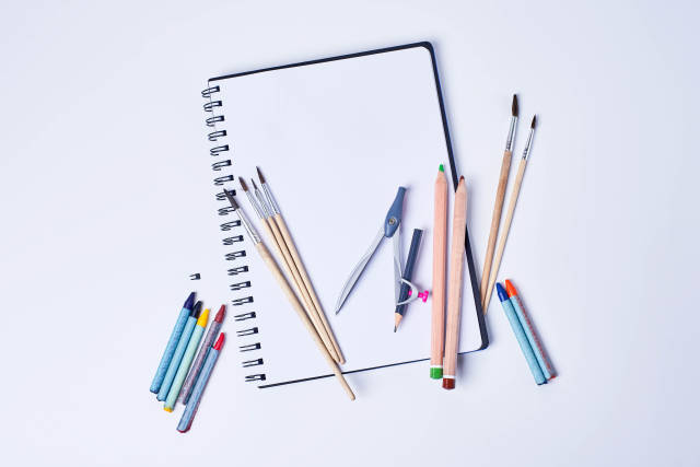 Open notepad with empty page and group of color pencils, brushes and compass