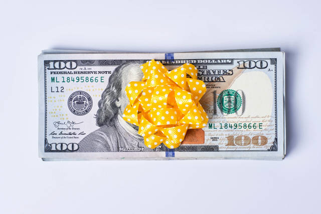 Money gift - Pile US dollar banknotes wrapped with bright yellow ribbon