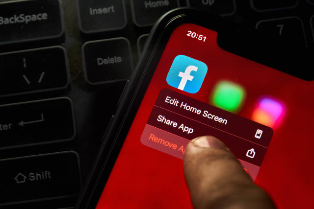 A person removing Facebook mobile application