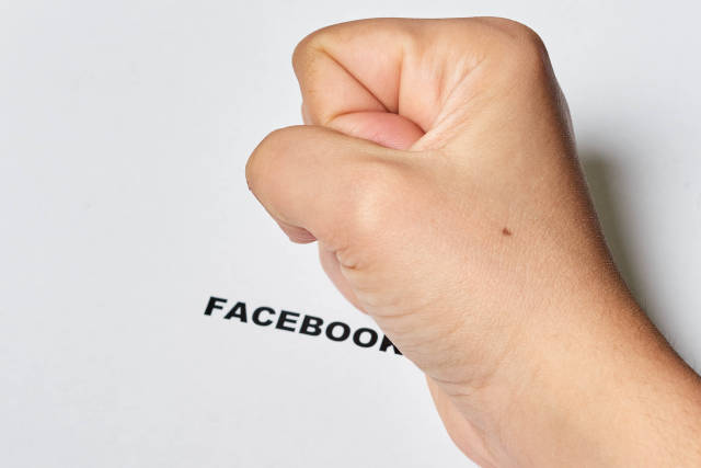 Fist of person on Facebook text. A person depressed by recent global Facebook crash