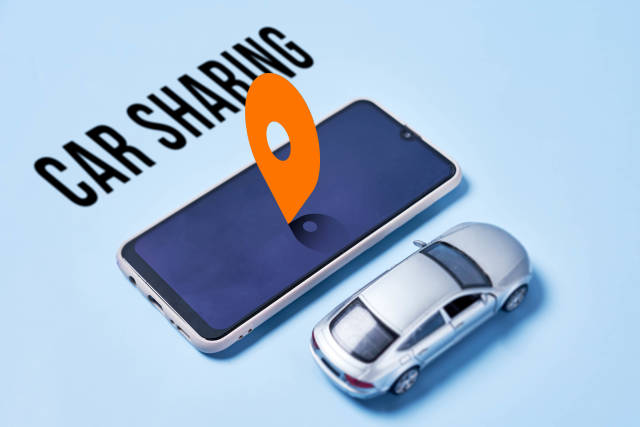 Car sharing with miniature automobile model and smartphone with location sign