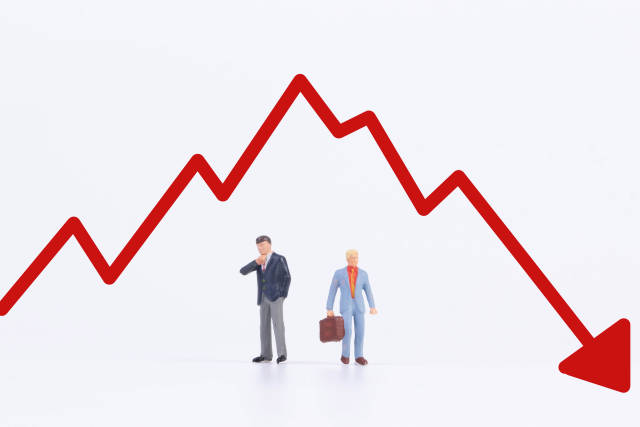 Two businessman with red down chart