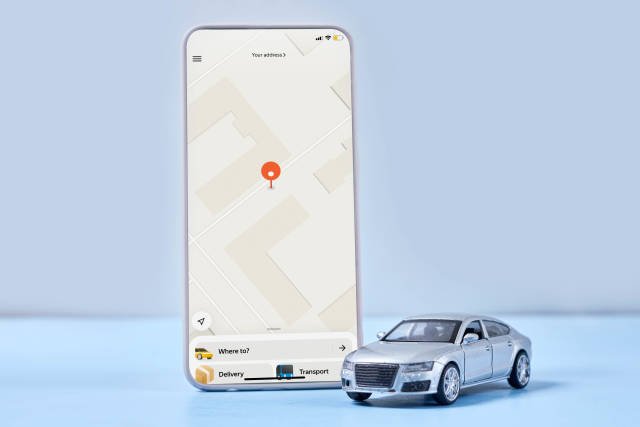 A smartphone with mobile taxi service application and car toy