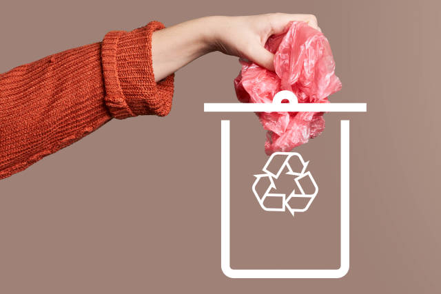 Hand throwing a plastic bag into drawn can. Concept of plastic recycling