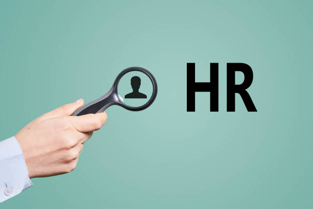 Hand holds a magnifying glass. HR, Hiring concepts