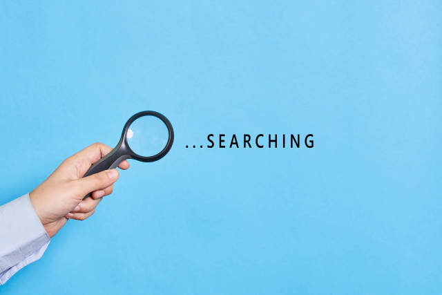 Searching. Hand of detective holding a magnifying glass